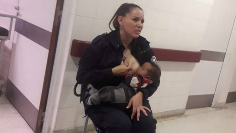 An on-duty police officer calms a crying baby - by breastfeeding him