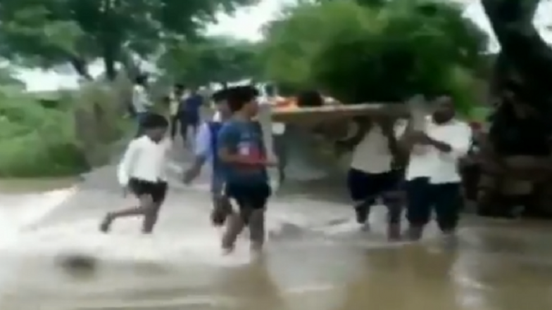 Madhya Pradesh: Villagers Carry Patient on Cot Across Flooded River Due to Bad Conditions of Roads in Damoh, Watch Video